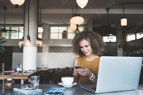 Handsome curly woman in city cafe, with cup of coffee and latop, using mobile phone