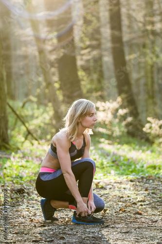 Fotobehang Fitness young woman runner tying shoelace outdoor