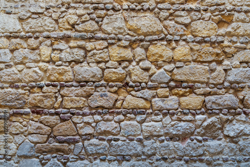 In de dag Baksteen muur Background of pattern of yellow and gray decorative grunge weathered uneven stone wall surface