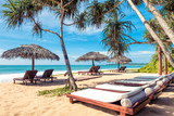 Beach beds with umbrellas on the tropical beach