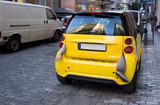 Small yellow city car with arm, leg hanging from boot