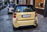 Small yellow city car with body parts hanging from boot