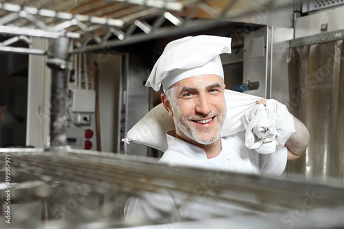Uśmiechnięty kucharz. Uśmiechnięty, szczęśliwy kucharz niesie worek z mąką
