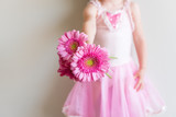 Cropped view of little girl in pink dance costume holding pink gerberas against neutral wall background (selective focus)