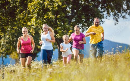 Rodzina, matka, ojciec i dzieci biegają dla sportu na łące