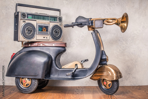 Plexiglas Scooter Retro radio with cassette tape recorder on old black toy scooter from circa 80s in front concrete textured wall background. Listening music concept. Vintage style filtered photo