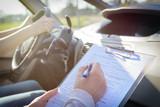 Examiner filling in driver's license road test form - 199934123