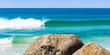 Praia com onda e rochas