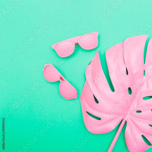 różowe okulary i liści palmowych tropikalnych monstera na zielonym tle. moda kreatywnych koncepcji. minimalizm i surrealizm