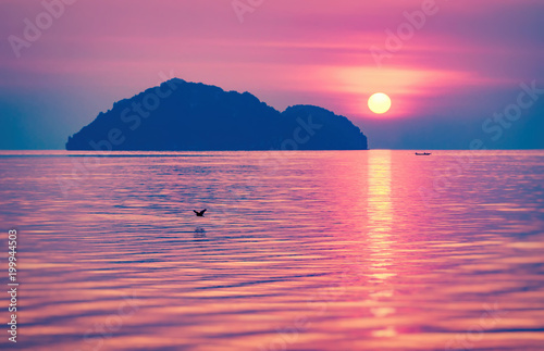Foto op Canvas Candy roze Beautiful sunset with reflection of the sunny path and silhouette of the island