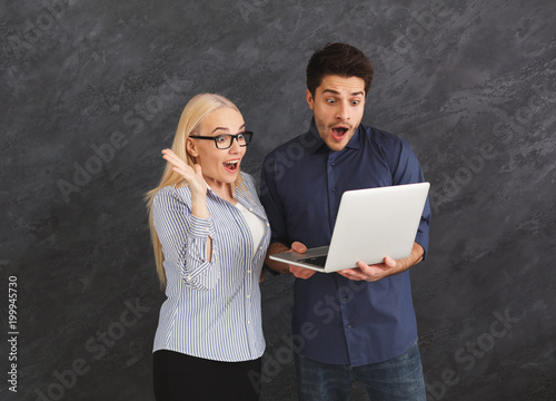 Shocked couple using laptop at studio