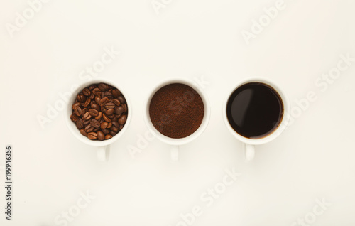 Foto op Aluminium Koffiebonen Roasted whole and ground coffee beans in cups, top view, white i