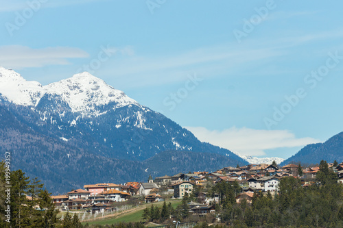 Fotobehang Pool Picturesque view on the village with high mountain peaks covered in snow on the background, Dolomites, Trentino, Italy