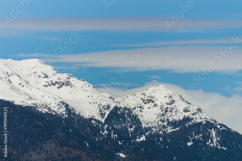 Foto op Aluminium Blauw Picturesque view of the high mountain peaks covered in snow with white clouds on the blue sky on the background, Dolomites, Trentino, Italy