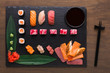 Set of assorted sushi, maki and rolls on rustic wooden background