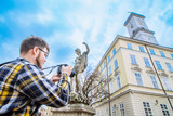 tourist with dslr camera taking picture of city hall. copy space