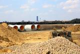 Materiały do budowy, piasek, żwir, róry betonowe na tle sky tower we Wrocławiu.