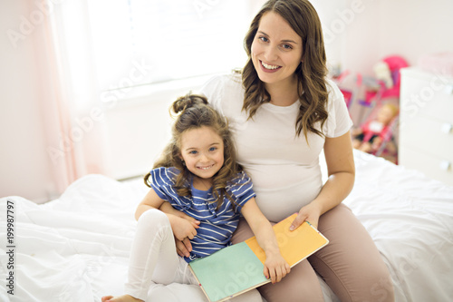 Portrait of a mother and daughter reading a book lying and relax in the bed