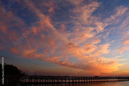 Golden and pink cloudscape at sunset over a wooden fishing pier jetty - 199993593