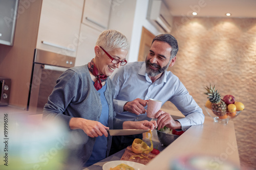 Romantic mature couple cooking together in the kitchen