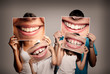 Leinwanddruck Bild - young family with children holding a picture of a mouth smiling on a gray background
