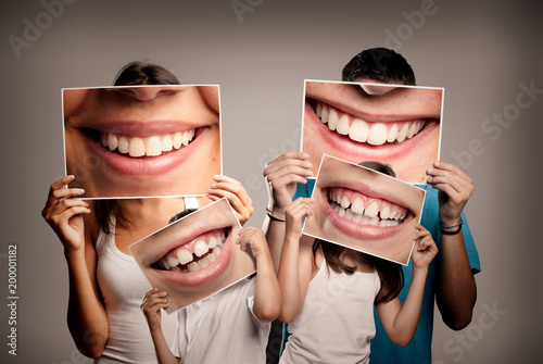 Leinwanddruck Bild young family with children holding a picture of a mouth smiling on a gray background