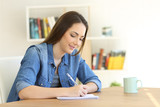 Girl writing in a notebook at home - 200001390