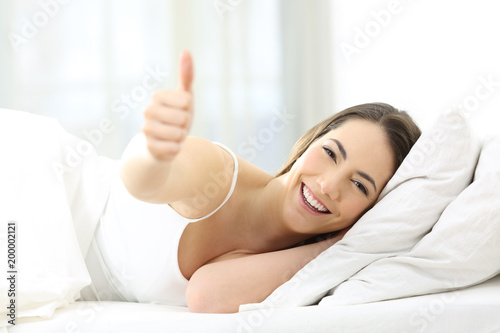 Happy woman with thumb up on the bed at home