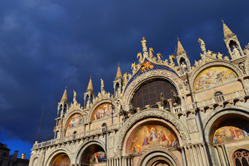 Beautiful gothic and byzantine facade of Saint Mark Basilica in Venice shines at sunset with cloudy sky