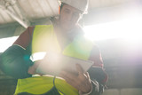 Low angle portrait of mature engineer wearing hardhat using digital tablet in workshop of modern industrial plant, copy space - 200002956