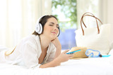 Woman listening to music relaxing in an hotel room - 200003984