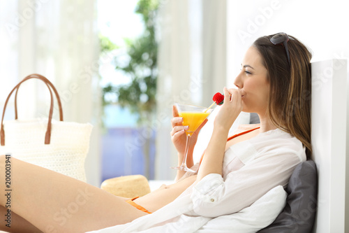 Woman drinking in an hotel room in summer vacations