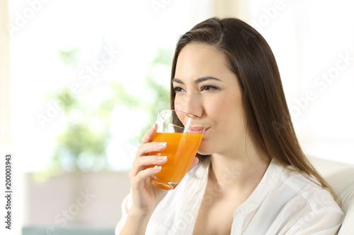 Woman drinking orange juice in a glass