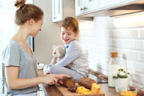 preparation of family breakfast. mother and child daughter cut bread and cheese in morning © JenkoAtaman