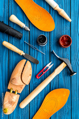 Foto Murales Instruments and materials for make shoes. Shoemaker's work desk. Hummer, awl, knife, sciccors, wooden shoe, insole, paint and leather. Blue wooden background top view pattern