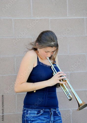 Female jazz trumpet player blowing her horn outside. Poster