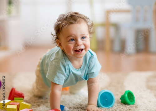Happy baby boy playing and crawling on the floor at home