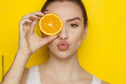 Young woman posing with slice of orange on her face on yellow background - 200050907