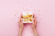 Leinwanddruck Bild - Womans hands holding gift or present box decorated confetti on pink pastel table top view. Flat lay composition for birthday or wedding.