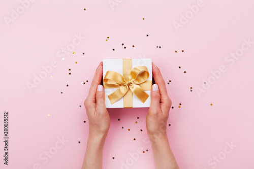 Leinwanddruck Bild Womans hands holding gift or present box decorated confetti on pink pastel table top view. Flat lay composition for birthday or wedding.