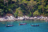 Traditional longtail boats and tourists snorkel in Thailand