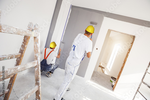 House painter paints a wall in a new home. Unrecognizable Person.