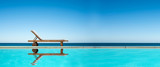 Reclining chair near a swimming pool, sea and blue sky panoramic background - 200083981