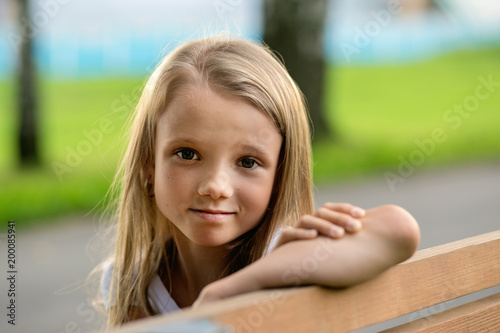 little girl with long hair sitting on bench in summer park