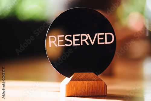 Indoor shot of reserved sig on wooden table in cafe, denotes that this place is occupied. Word reserved written in capital letters. Don`t sit there, please!