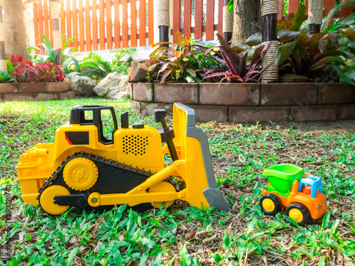 Fotobehang Trekker children baby toys tractor and truck in the beautiful garden forest playground nature light flare outdoor