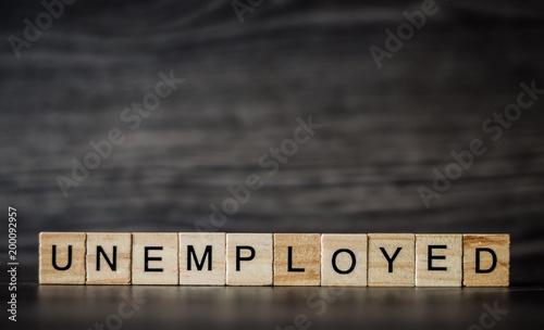 słowo bezrobotni, składające się z lekkich drewnianych kwadratowych paneli na ciemnym drewnianym tle