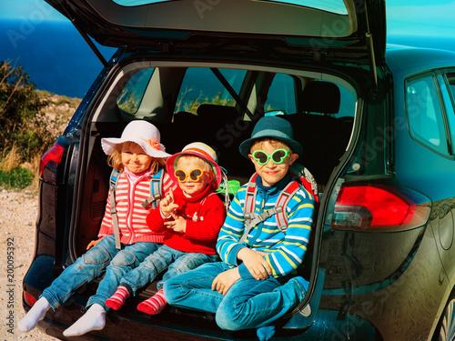 happy kids- little boy and girls- enjoy travel by car at beach