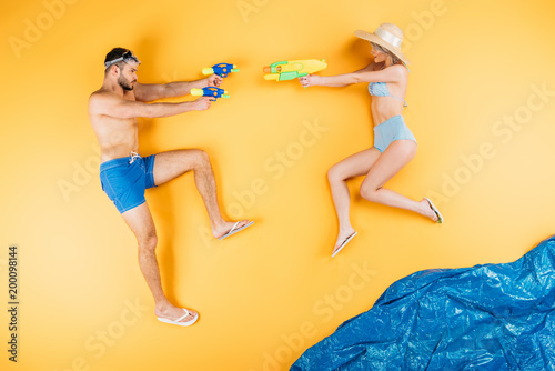 young couple in swimwear playing with water guns on yellow