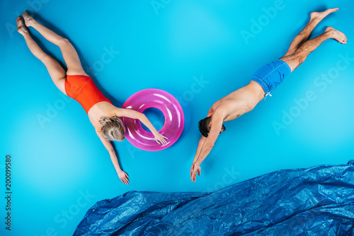 young couple swimming in imagine sea on blue, summer vacation concept